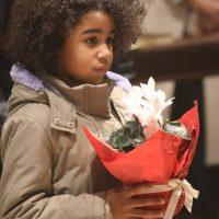 Una bambina offre un fiore, simbolo della freschezza della vita